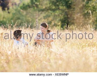 Smiling couple relaxing in wheatfield - Stock Photo