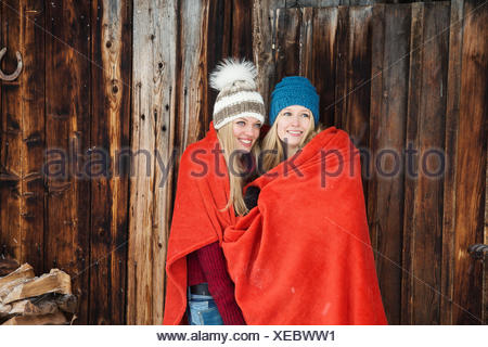 Two young female friends wrapped in red blanket outside wooden cabin - Stock Photo