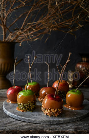 Marble tray full of caramel apples with stick handles covered in nuts and seeds. Moody fall foliage in the background. - Stock Photo