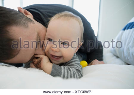 Father kissing smiling baby boy on bed - Stock Photo