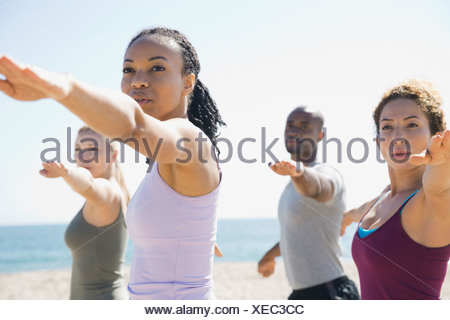 Group performing yoga on beach - Stock Photo