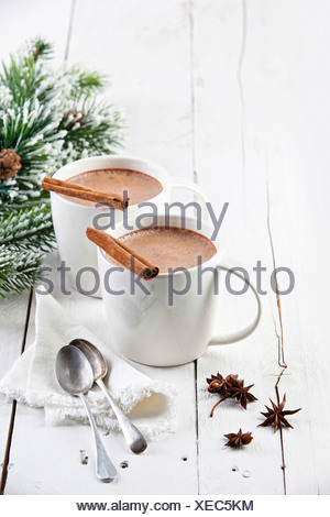 Hot cocoa with cinnamon sticks on white wooden background - Stock Photo