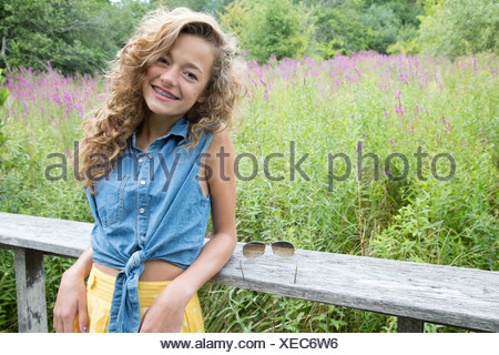 Portrait of teenage girl leaning on wooden fence - Stock Photo