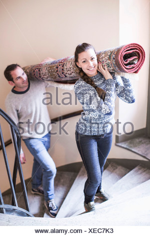 Portrait of young woman with man carrying rolled carpet up stairs - Stock Photo