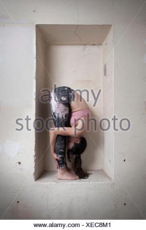 Mid adult woman practicing uttanasana pose in alcove, Munich, Bavaria, Germany - Stock Photo
