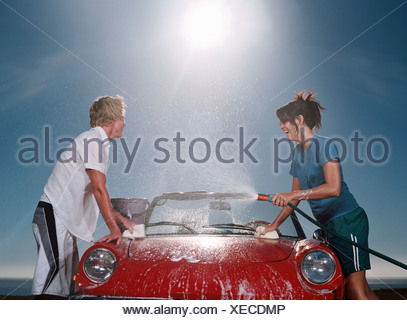 Young people washing car - Stock Photo