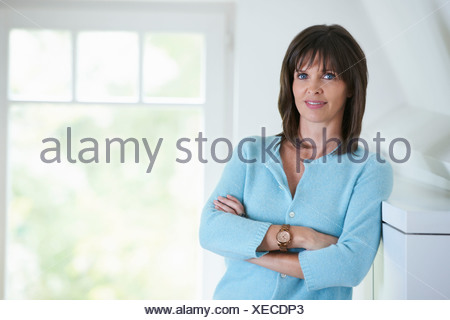 Businesswoman standing in office interior, arms folded - Stock Photo