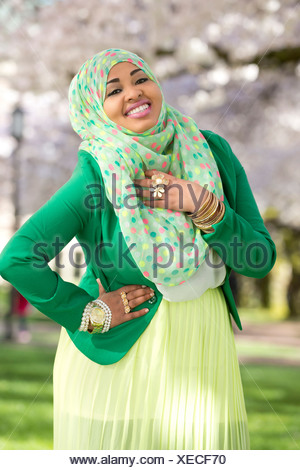 Portrait of young female in park wearing green - Stock Photo