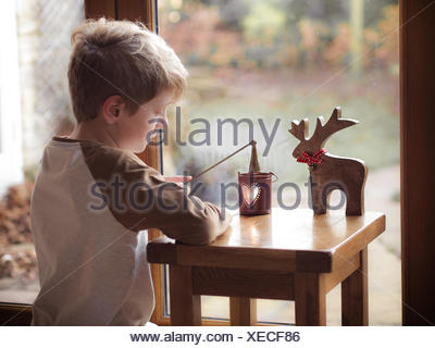 Boy (6-7) putting candle out of lantern - Stock Photo
