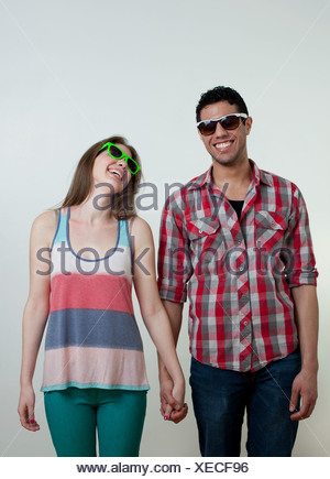 Young couple wearing sunglasses and laughing, studio shot - Stock Photo