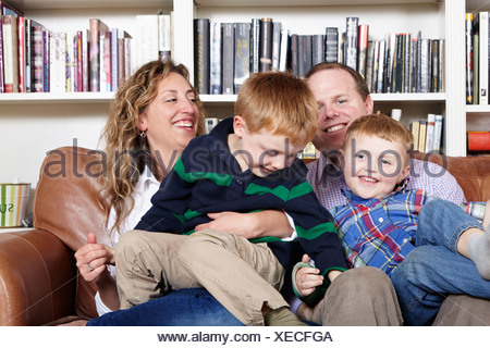 Mid adult parents and young sons sitting on sofa - Stock Photo