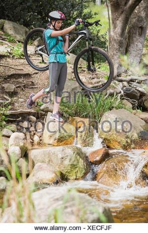Woman carrying her bike - Stock Photo
