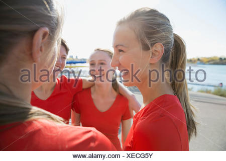 Rowing team talking in huddle - Stock Photo