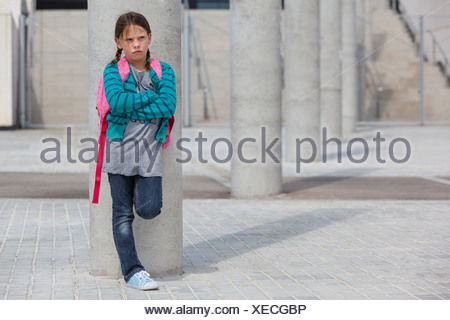 Frowning girl leaning against column - Stock Photo