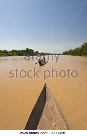Black Volta river Ghana Men paddling canoe upstream black Voltriver Ghana - Stock Photo