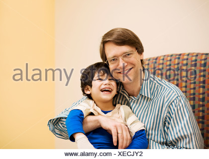 Father holding disabled son in doctor's office - Stock Photo
