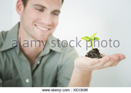 Man holding seedling - Stock Photo