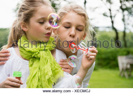 Two sisters blowing bubbles - Stock Photo