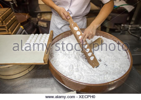 A small artisan producer of wagashi pressing the mixed dough into moulds - Stock Photo