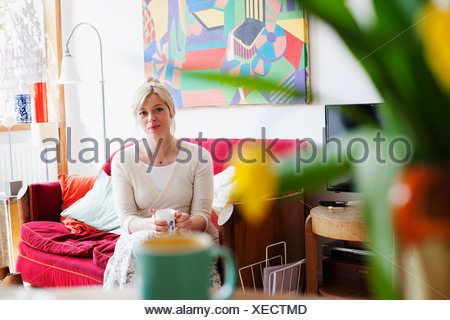 Young woman relaxing in living room with cup of tea - Stock Photo