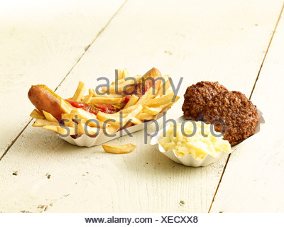 Curry sausage with French fries, two meatballs and mashed potatoes on wooden table - Stock Photo