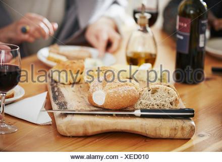 Freshly baked bread on breadboard, close up - Stock Photo