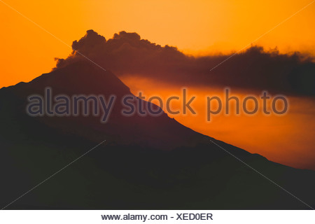 Alaska. Mt. Redoubt emitting steam and ash at sunset, as viewed from Kenai. - Stock Photo