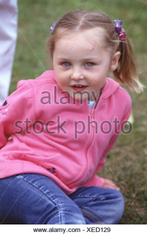 MFemale child blonde hair off face in bunches wearing pink zip up hooded top blue jeans sitting on grass looking to camera - Stock Photo