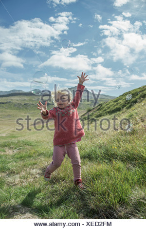 Young girl running to catch bubbles - Stock Photo