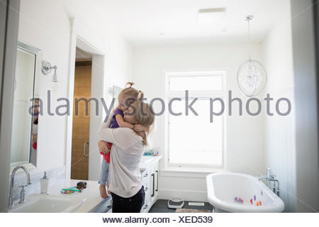 Mother hugging daughter at bathroom counter - Stock Photo