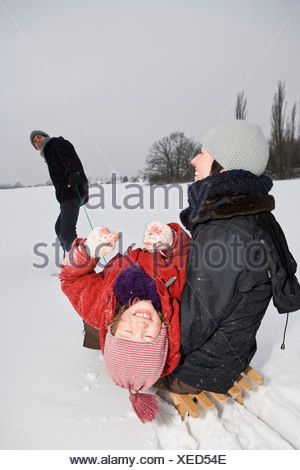 A man pulling a sled with his wife and daughter on it - Stock Photo