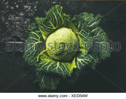 Raw fresh green cabbage over dark background, top view, selective focus, horizontal composition - Stock Photo