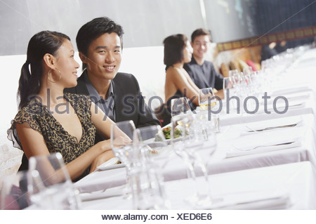 Couples dining in restaurant, man smiling at camera - Stock Photo
