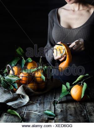 Woman peeling a orange - Stock Photo