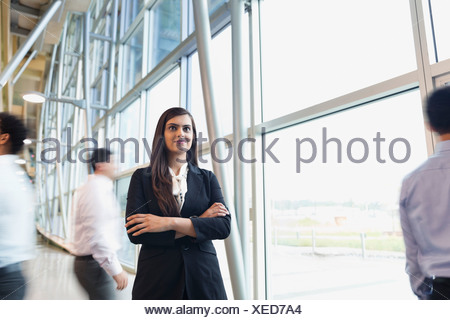 Confident business woman standing with arms crossed - Stock Photo