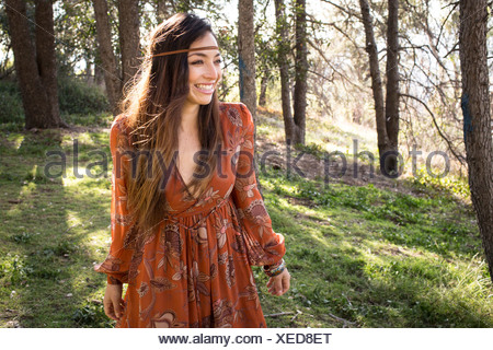 Portrait of young woman wearing dress in forest, smiling - Stock Photo