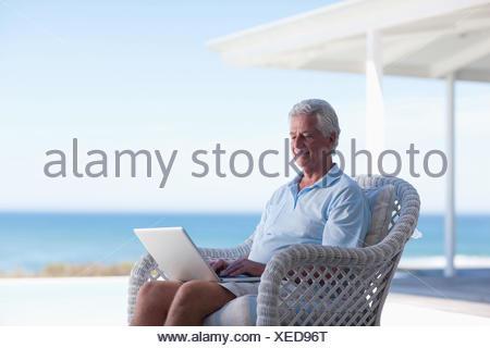 Senior man using laptop on beach patio - Stock Photo