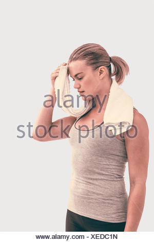 Composite image of muscular woman wiping herself with towel - Stock Photo