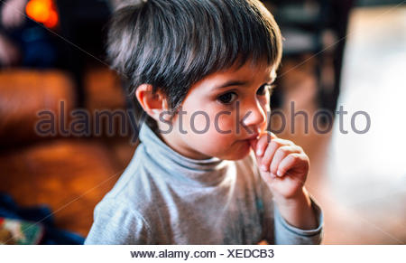 Portrait of little boy with finger in his mouth - Stock Photo
