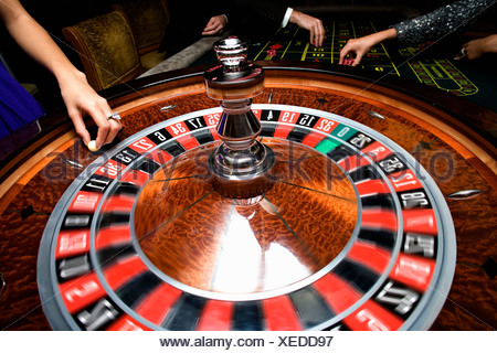 People gambling at roulette table, mid section - Stock Photo