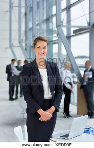 Portrait of smiling businesswoman in suit standing next to laptop in lobby - Stock Photo