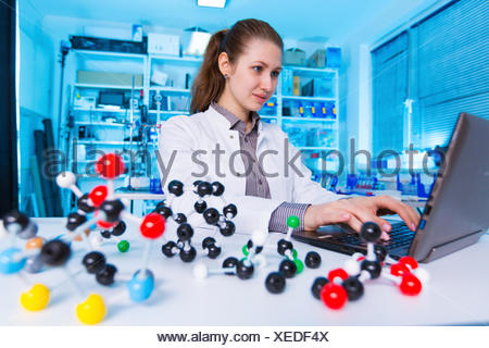 MODEL RELEASED. Female chemist using laptop in the laboratory. - Stock Photo