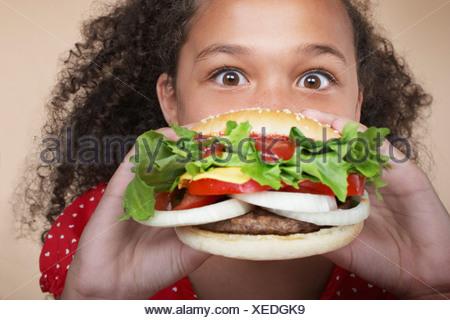 Young girl indoors eating a hamburger - Stock Photo