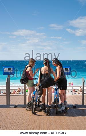 Teenage girls on rollerblades beside bicycles on the Promenade des Anglais, Nice, Provence, France - Stock Photo