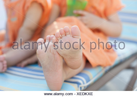 Girl's feet on sun lounger, close up - Stock Photo