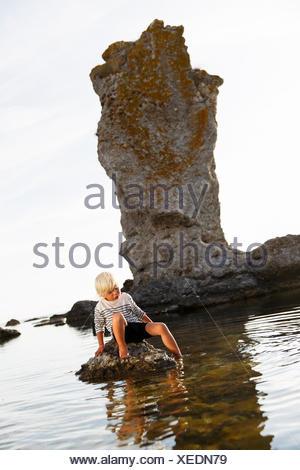 Sweden, Gotland, Faro, Blonde little boy (2-3) sitting on rock with one leg in water - Stock Photo