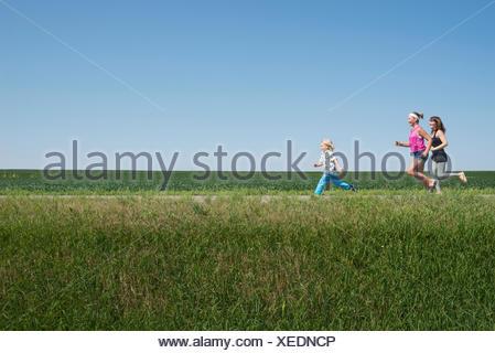 Three people running through field - Stock Photo