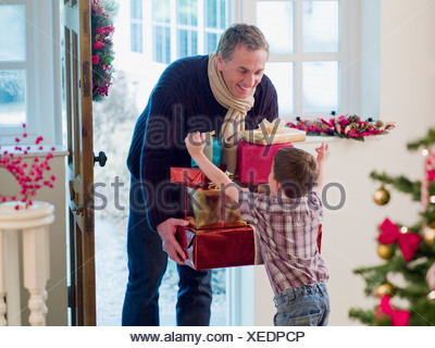 Boy running to father holding Christmas gifts in doorway - Stock Photo