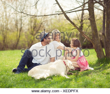 Family sitting in park with dog - Stock Photo