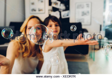 Happy mother with daughter at home blowing soap bubbles - Stock Photo